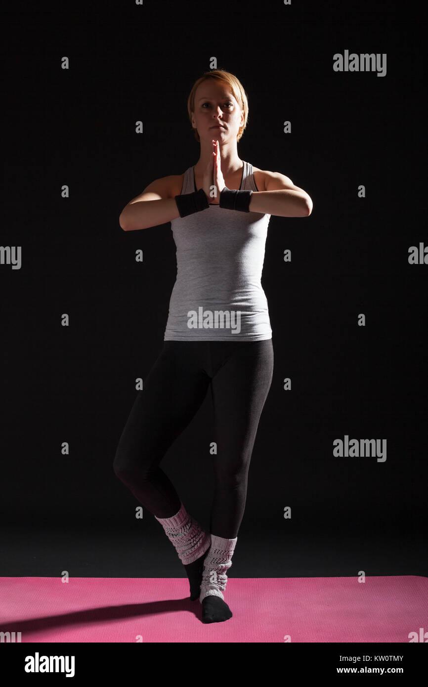 Young woman practicing yoga, Garudasana / Eagle pose - Stock Image