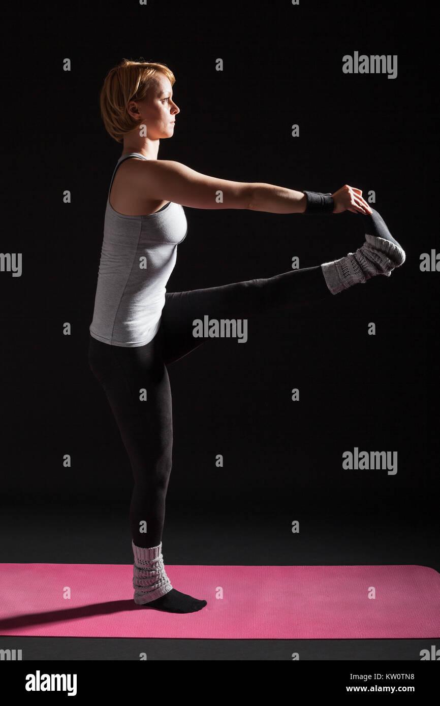Young woman practicing yoga, Padangusthasana / Hand to big toe pose - Stock Image