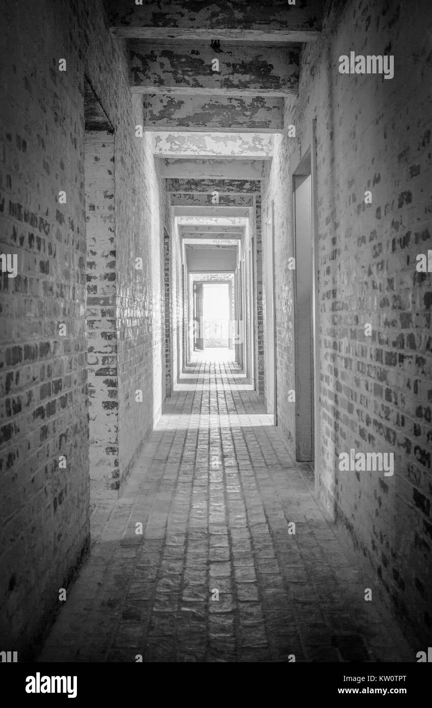 Light At The End Of The Tunnel. Long brick hallway with bright light shining through the open door at the end in - Stock Image