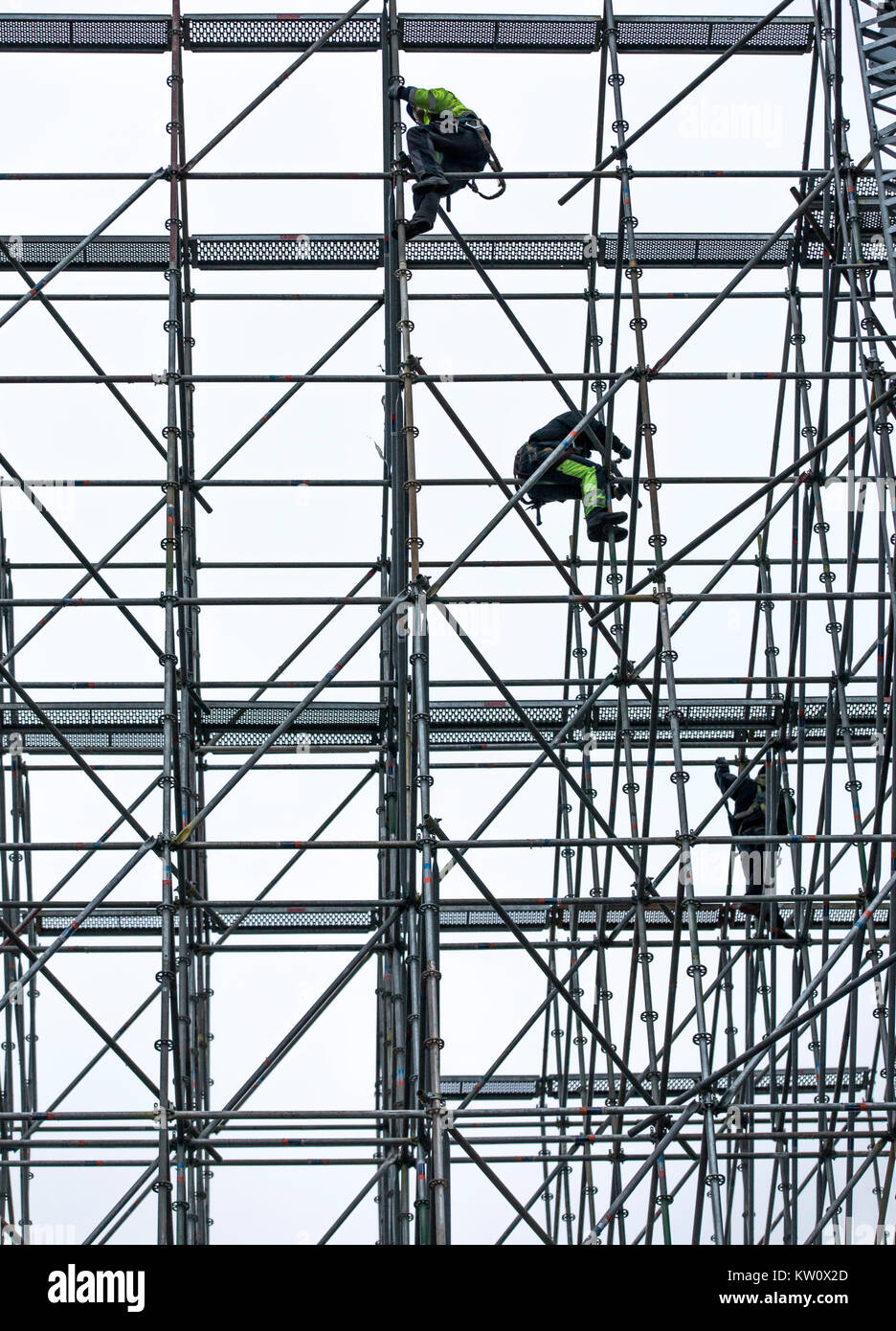 Scaffolders at work, building a large scaffolding, work at high altitude, - Stock Image