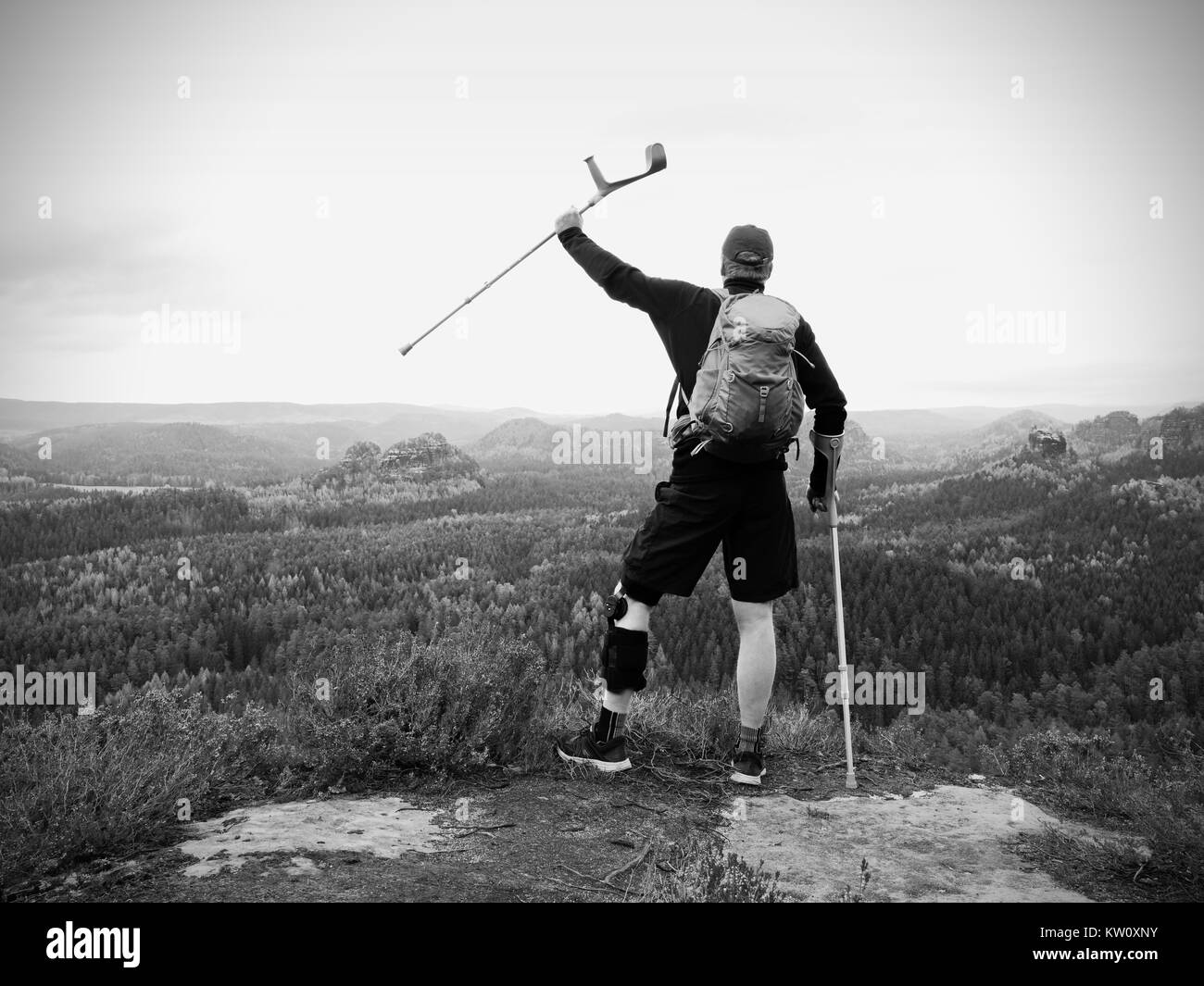 Wounded tourist with crutch above head achieved mountain peak. Hiker with backpack and  knee brace feature. Deep - Stock Image