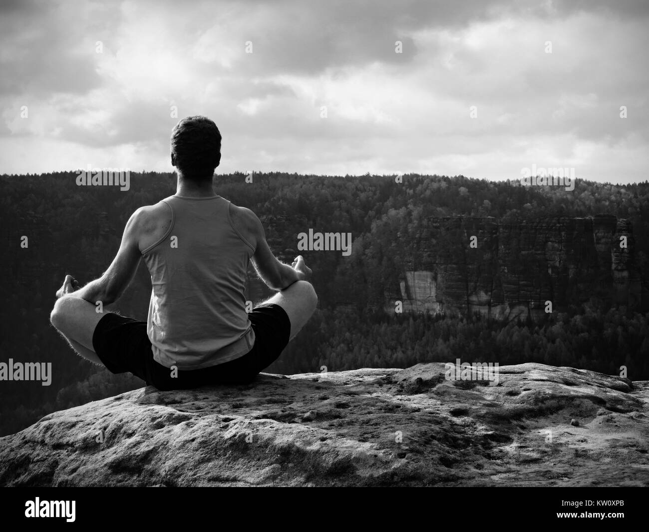 Man meditating in Lotus Pose on rocky cliff. Sportsman practicing Yoga on stone edge above landscape - Stock Image