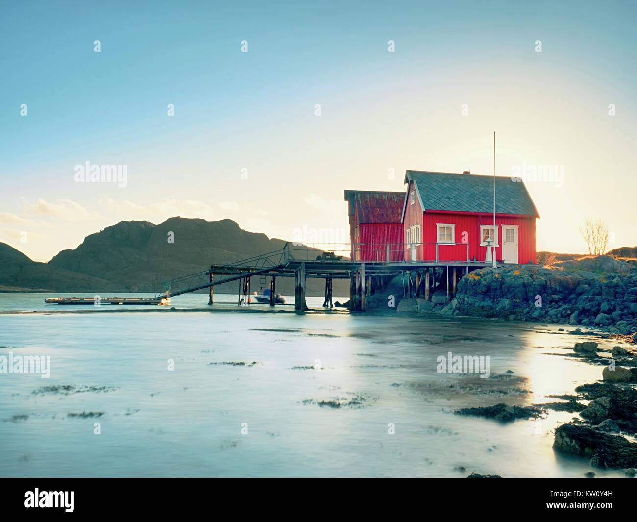 Norwegian coast landscape with a typical red house.  Wooden red house on the seaside, first warm spring day. - Stock Image