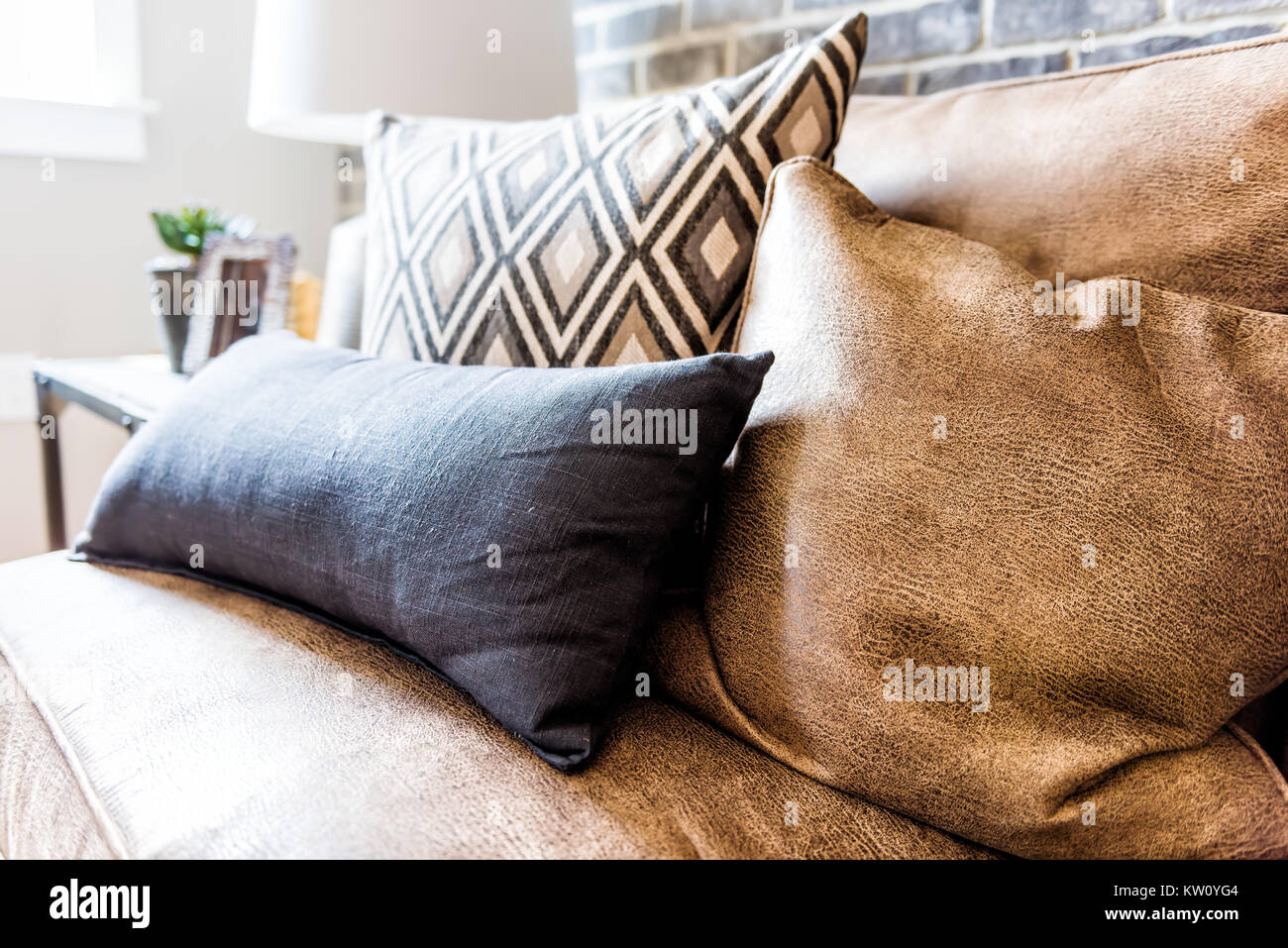 Elegant modern room closeup of leather couch and pillows in staging model house, home or apartment Stock Photo