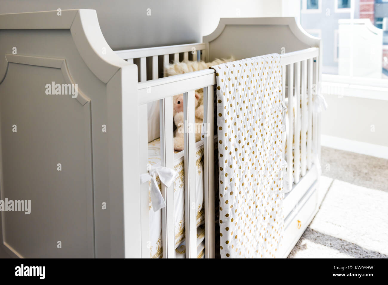 Closeup of bright yellow baby crib in nursery room in model staging home, apartment or house, toy - Stock Image