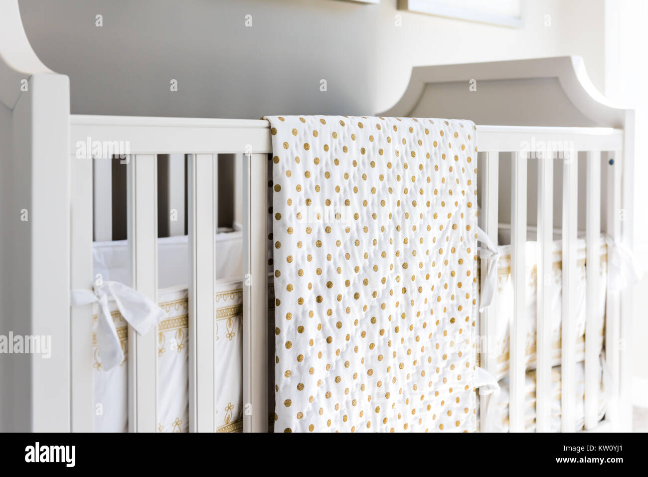 Closeup of bright yellow baby crib in nursery room in model staging home, apartment or house - Stock Image