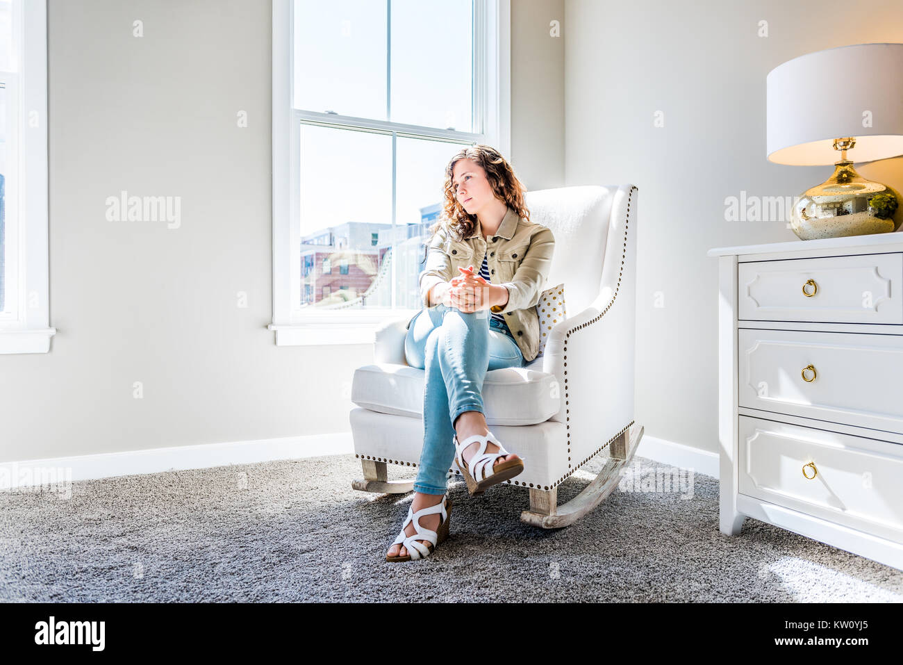 Bright white modern rocking chair in nursery room with chest of drawers, decorations in model staging home, apartment - Stock Image