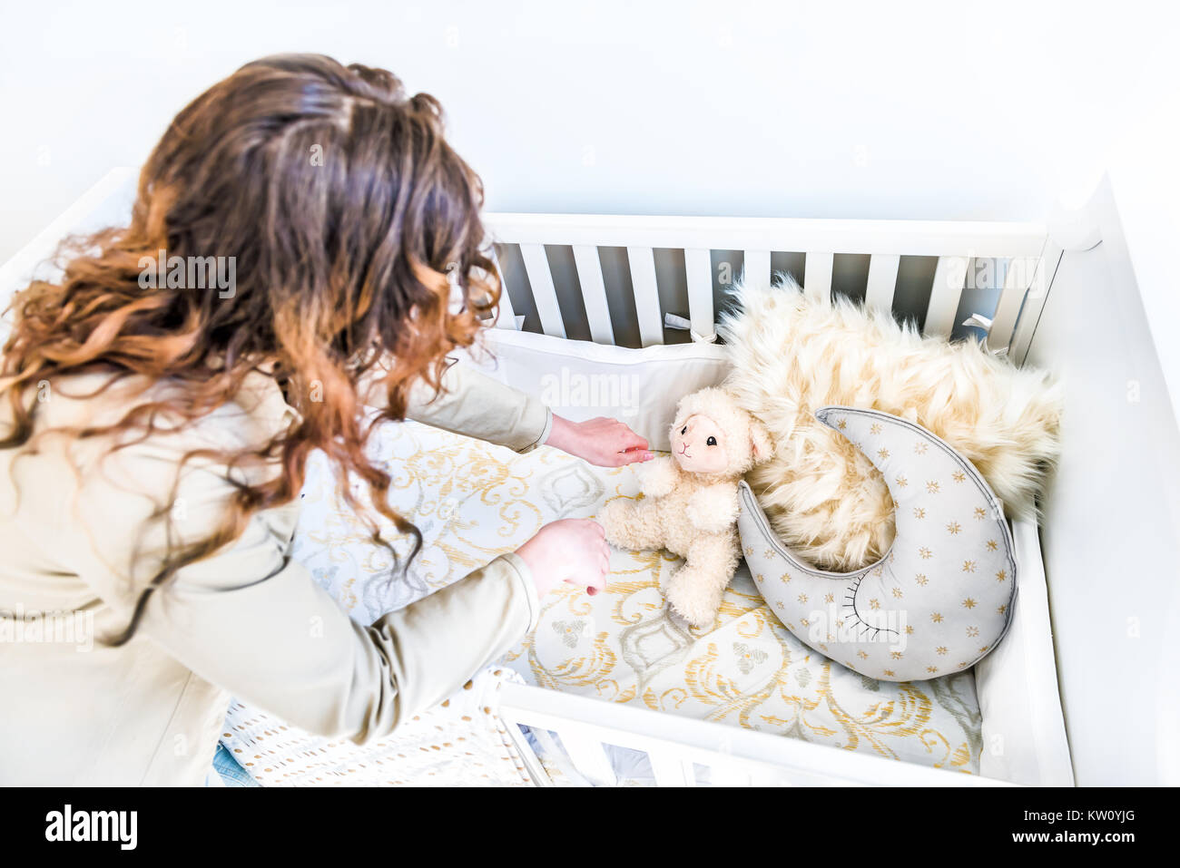 Closeup of bright yellow baby crib in nursery room with young woman in model staging home, apartment or house setting - Stock Image