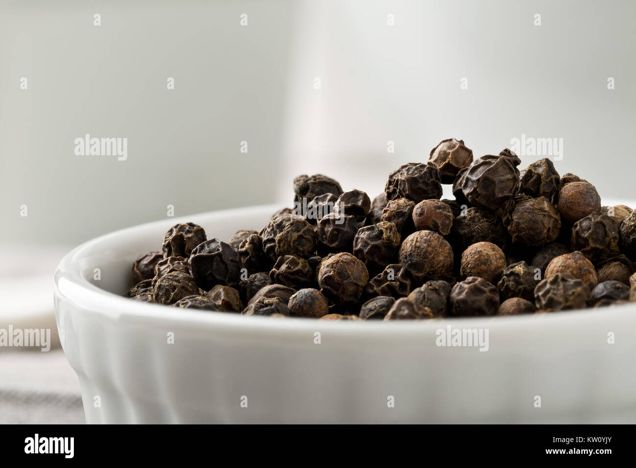 Raw, natural, unprocessed black pepper peppercorns white bowl on kitchen table - Stock Image