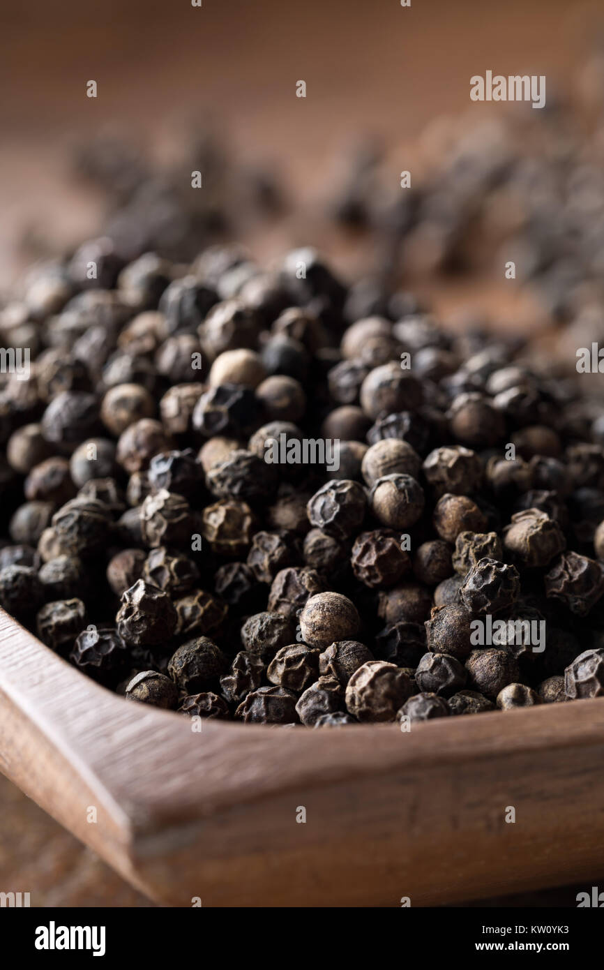 Raw, natural, unprocessed black pepper peppercorns on wooden plate with selective focus - Stock Image