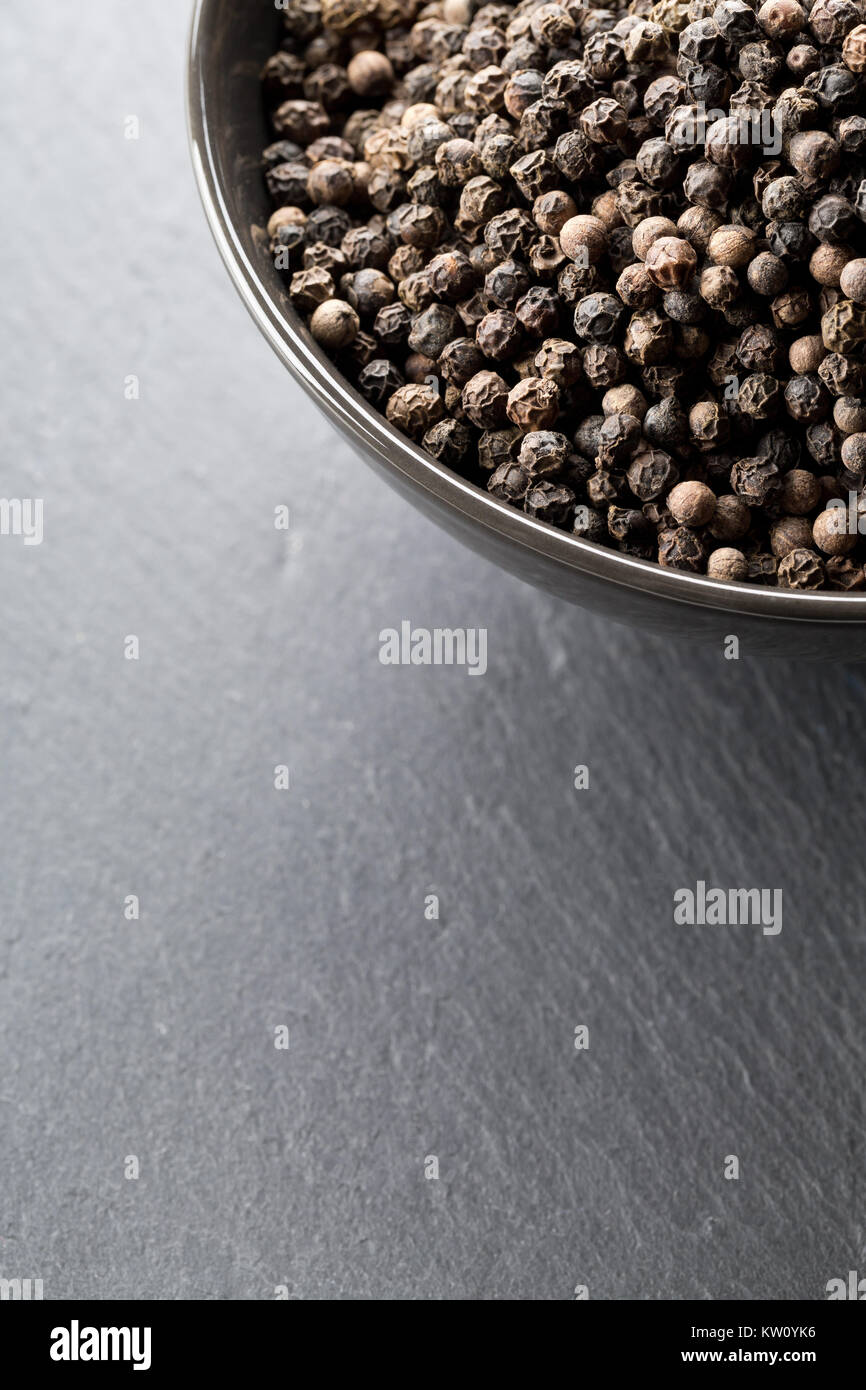 Raw, natural, unprocessed black pepper peppercorns in black bowl on dark stone background - Stock Image