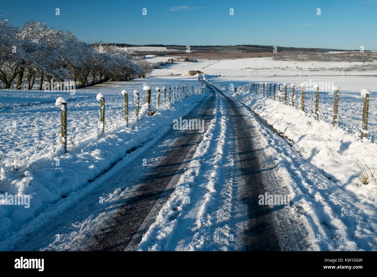 Snow covered back road through farmland near Forth, Lanarkshire, Scotland - Stock Image