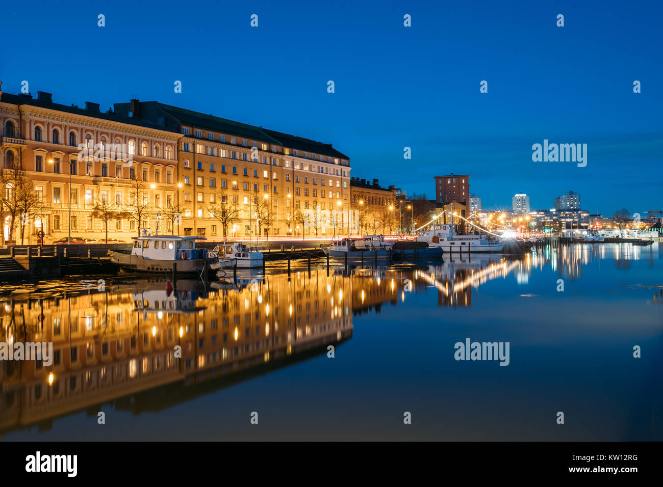 Helsinki, Finland. View Of Pier With Boats And Pohjoisranta Street In Evening Night Illuminations. - Stock Image