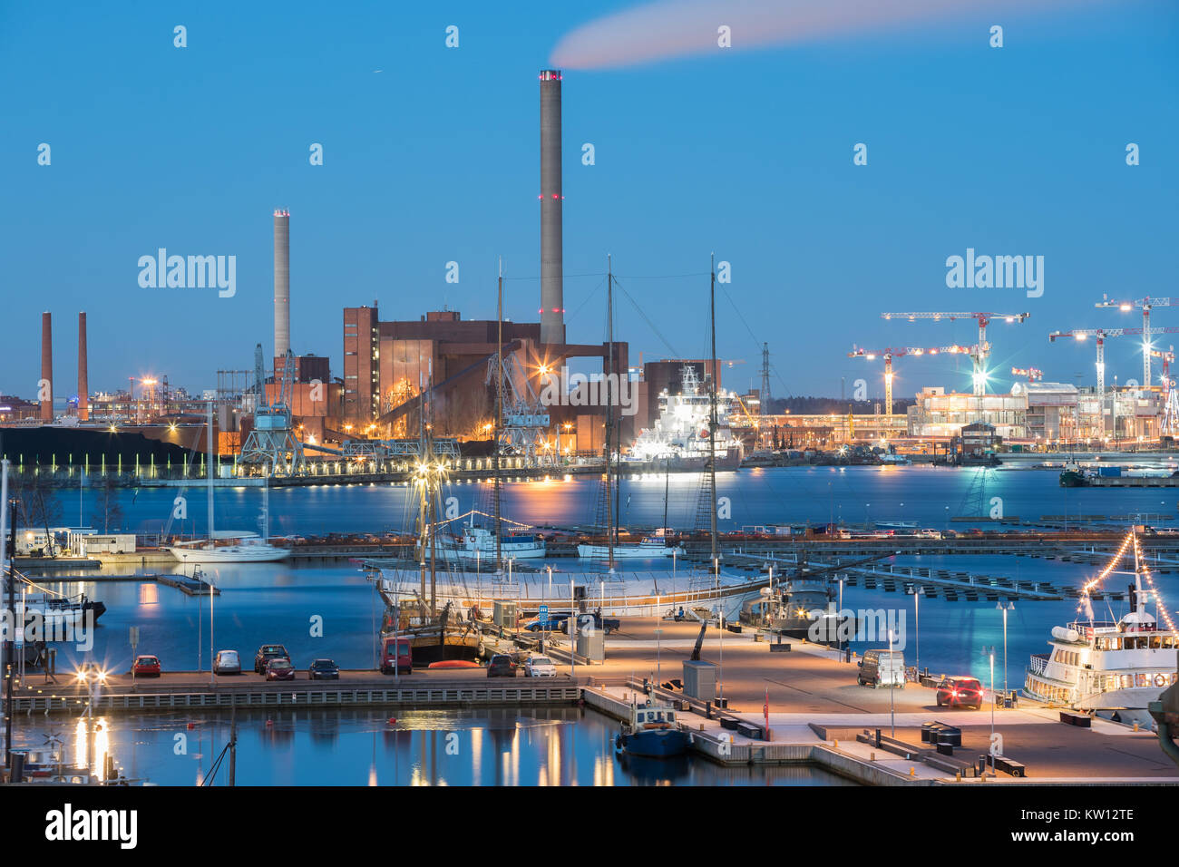 Helsinki, Finland. Evening Night View Of Industrial Zone Of Hanasaari Power Plant And Pier, Berth With Moored Ships, - Stock Image