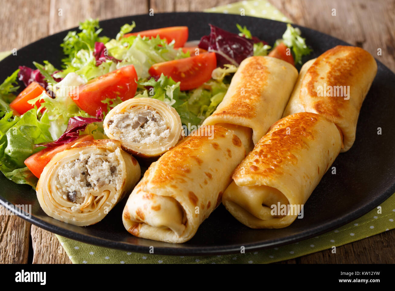 crepes rolls with chicken, cheese and mushrooms close-up and salad of fresh vegetables on a plate. horizontal - Stock Image