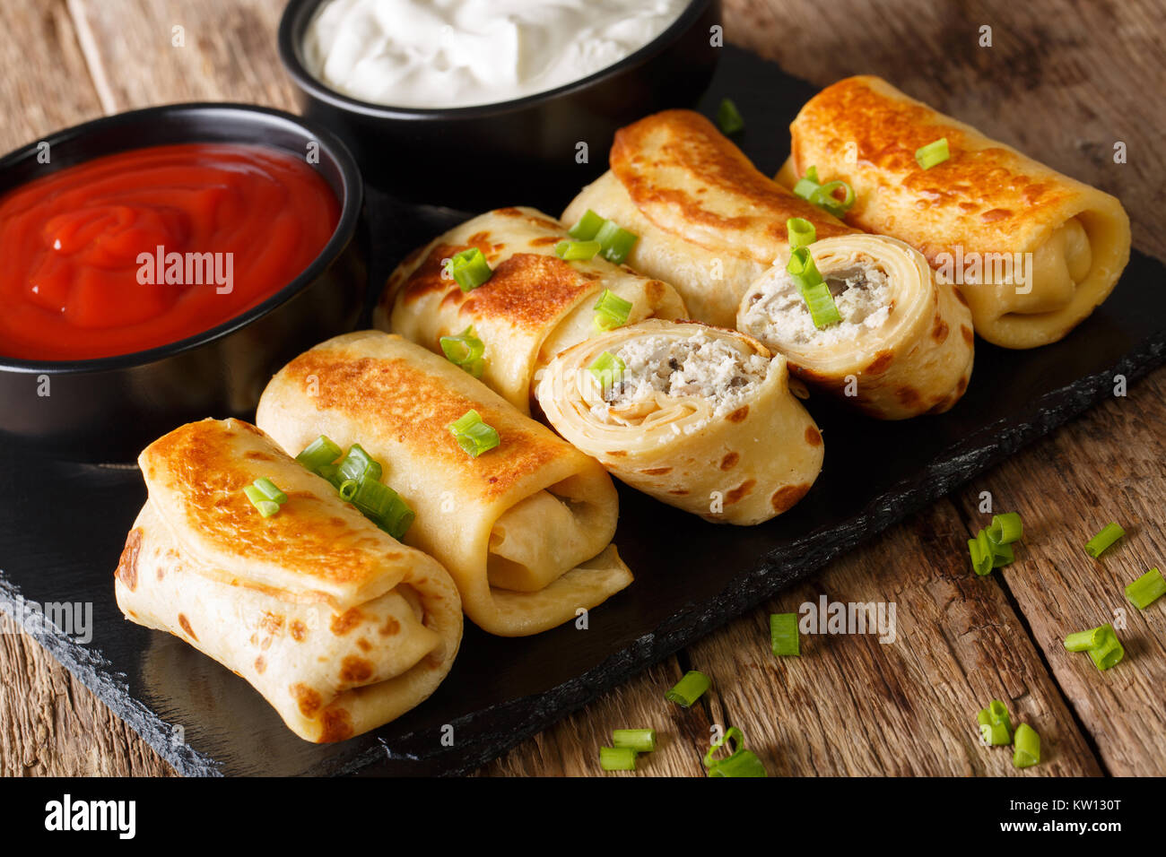 Pancakes rolls stuffed with chicken and mushrooms close-up and tomato sauce, sour cream on the table. horizontal - Stock Image