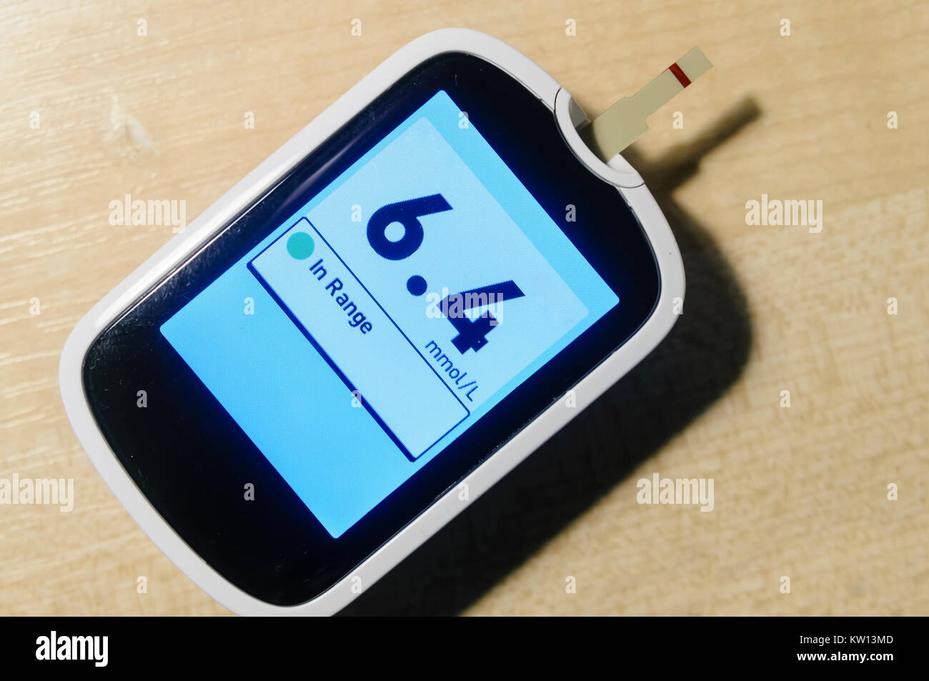 Blood glucose monitor showing a glucose level of 6.4 mmol/L - Stock Image