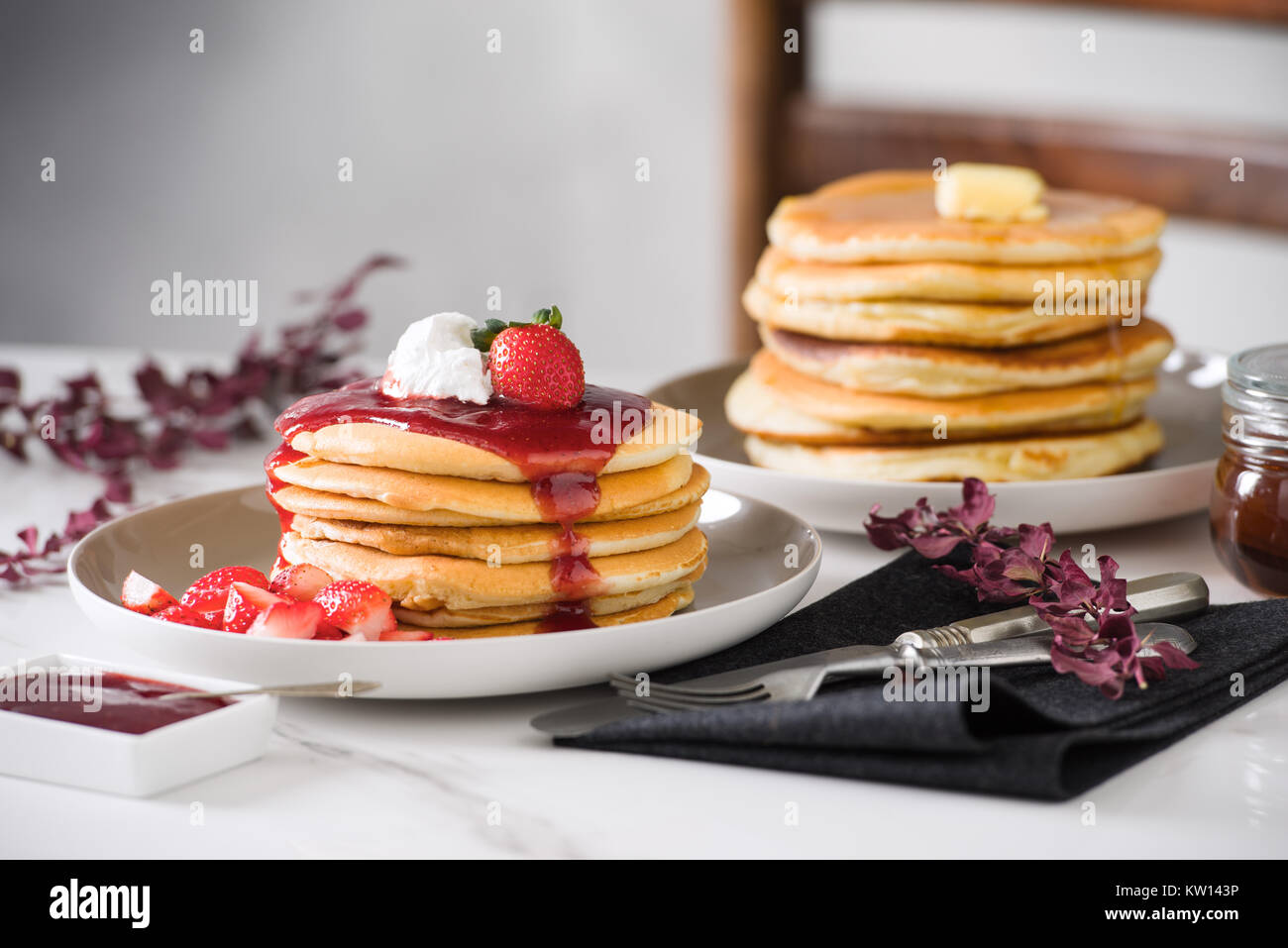 fluffy Pancakes with butter , syrup, cream and strawberry syrup topping. daylight, breakfast, morning, stone background, - Stock Image