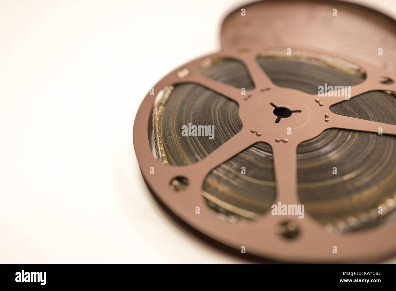 100 foot reel of 8mm home movie film, showing damaged caused by acetic acid degredation, isolated on a white background, - Stock Image