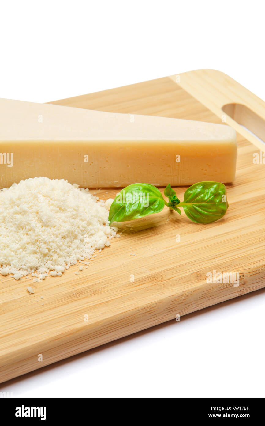 a piece of Parmesan and grated cheese on cutting board white background - Stock Image