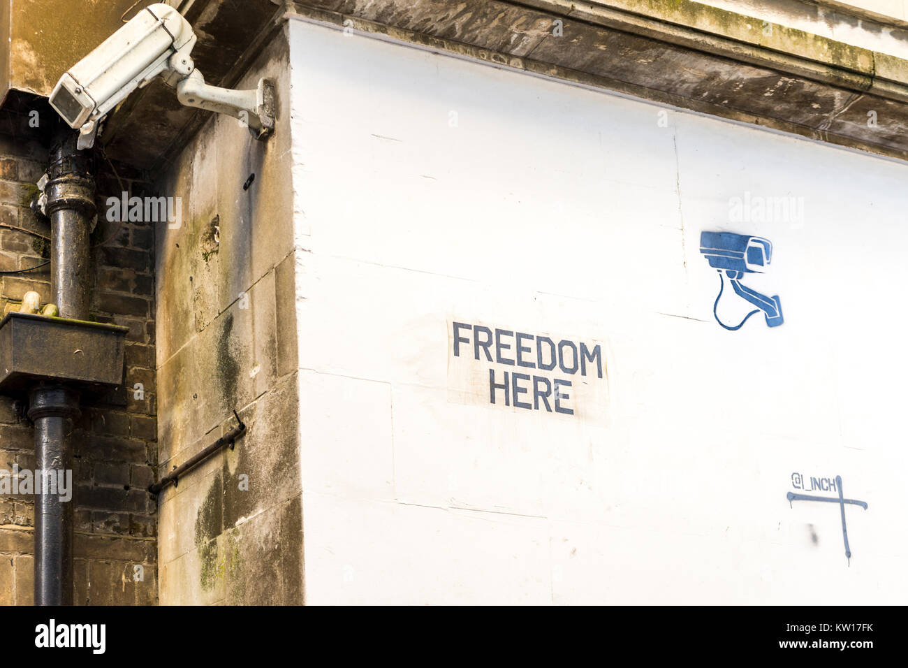 Stencil art graffiti 'Freedom' concept on a white wall with a surveillance camera next to it in Southampton - Stock Image