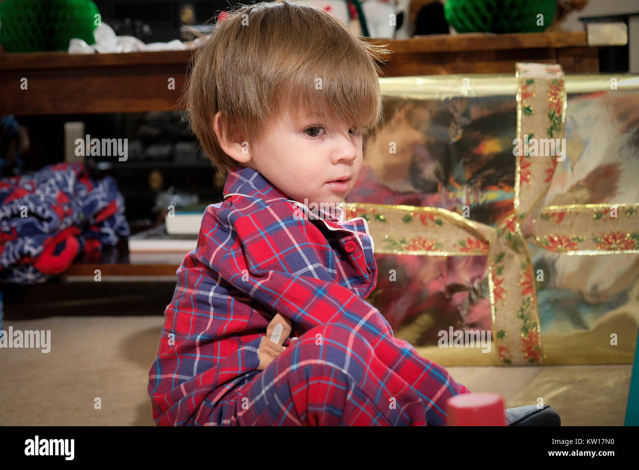 toddler sat on floor in his pajamas playing with toys on Christmas morning - Stock Image