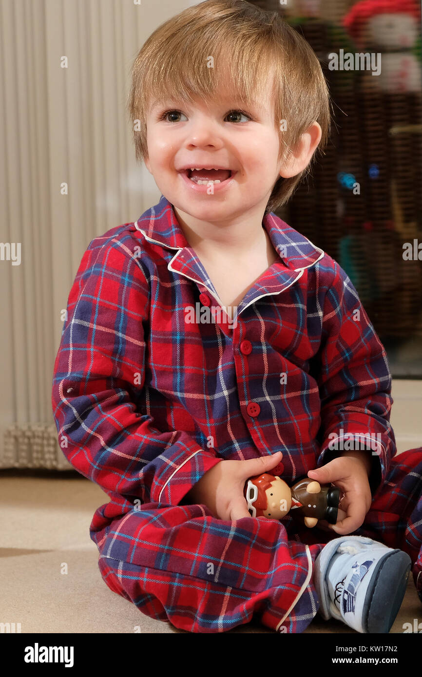 Happy toddler boy in pajamas playing with toy and smiling happily - Stock Image