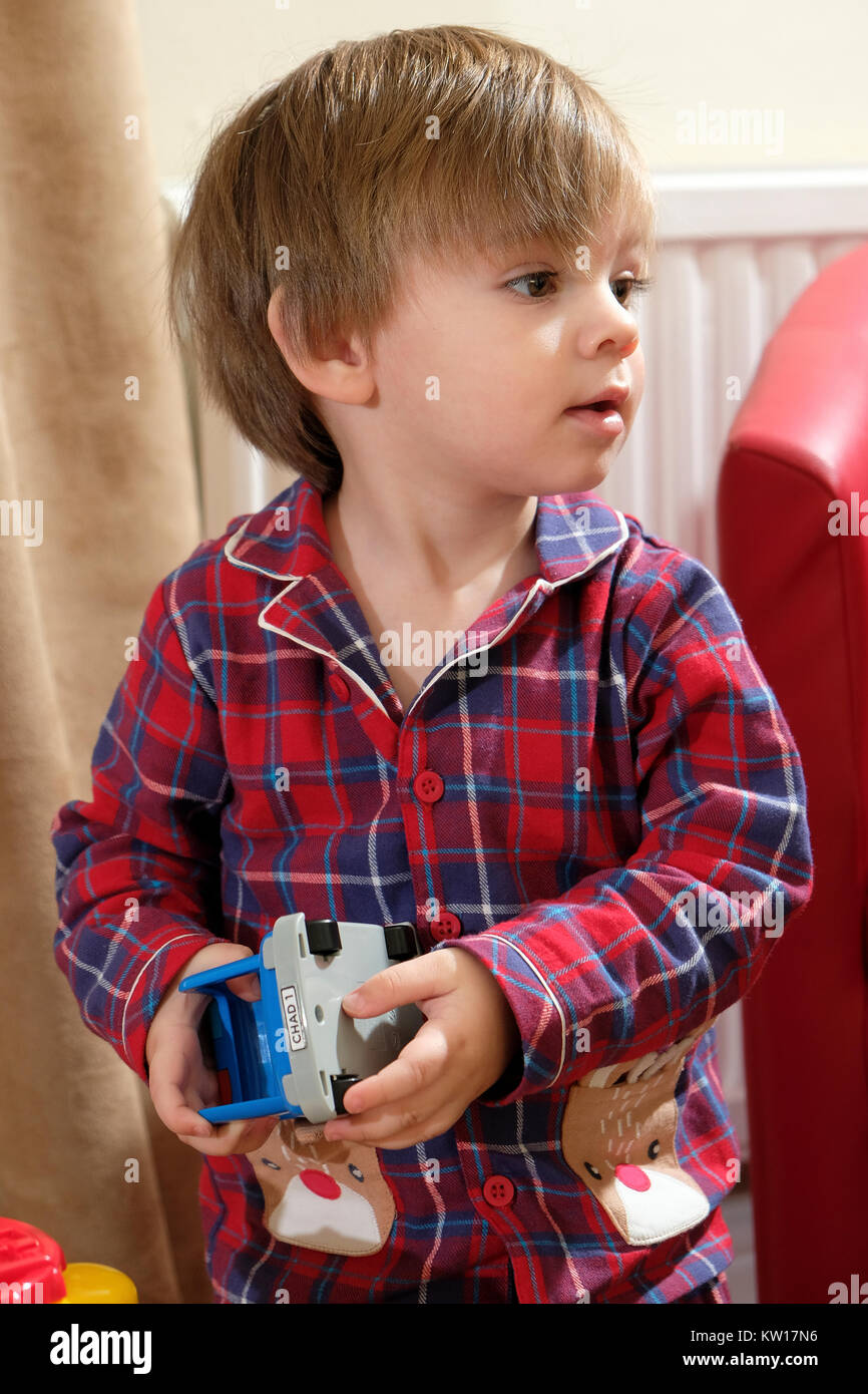 Young, toddler boy in pajamas playing with toy car - Stock Image