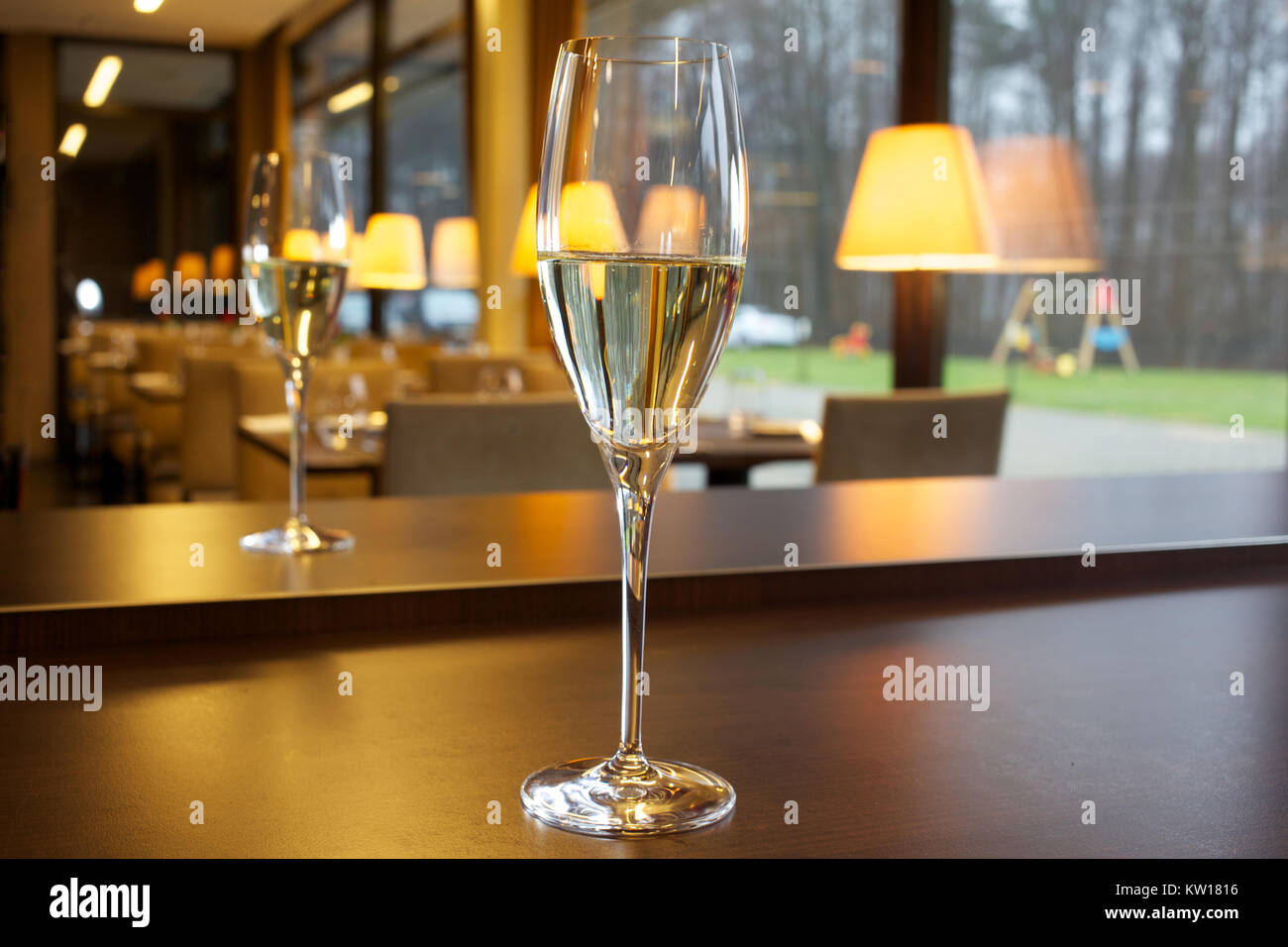 Glass of champagne on the table in the restaurant. - Stock Image