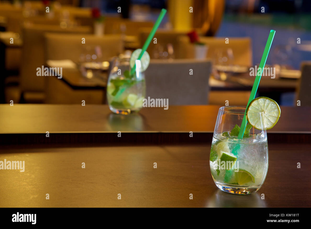 Mojito cocktail on wooden table at a cafe blurred background - Stock Image