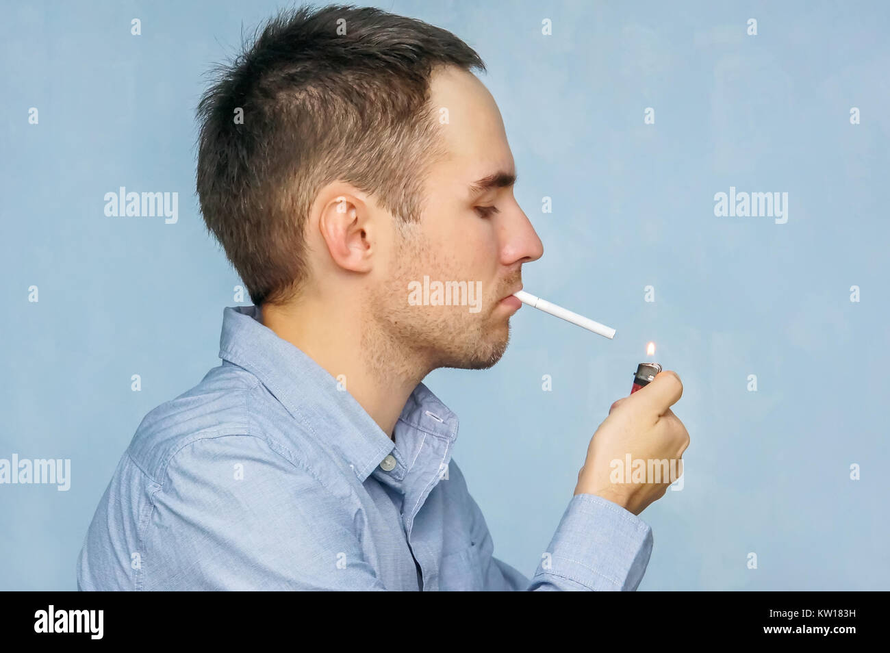 man smoking a cigarette. The guy in the blue shirt lights up from the fire - Stock Image