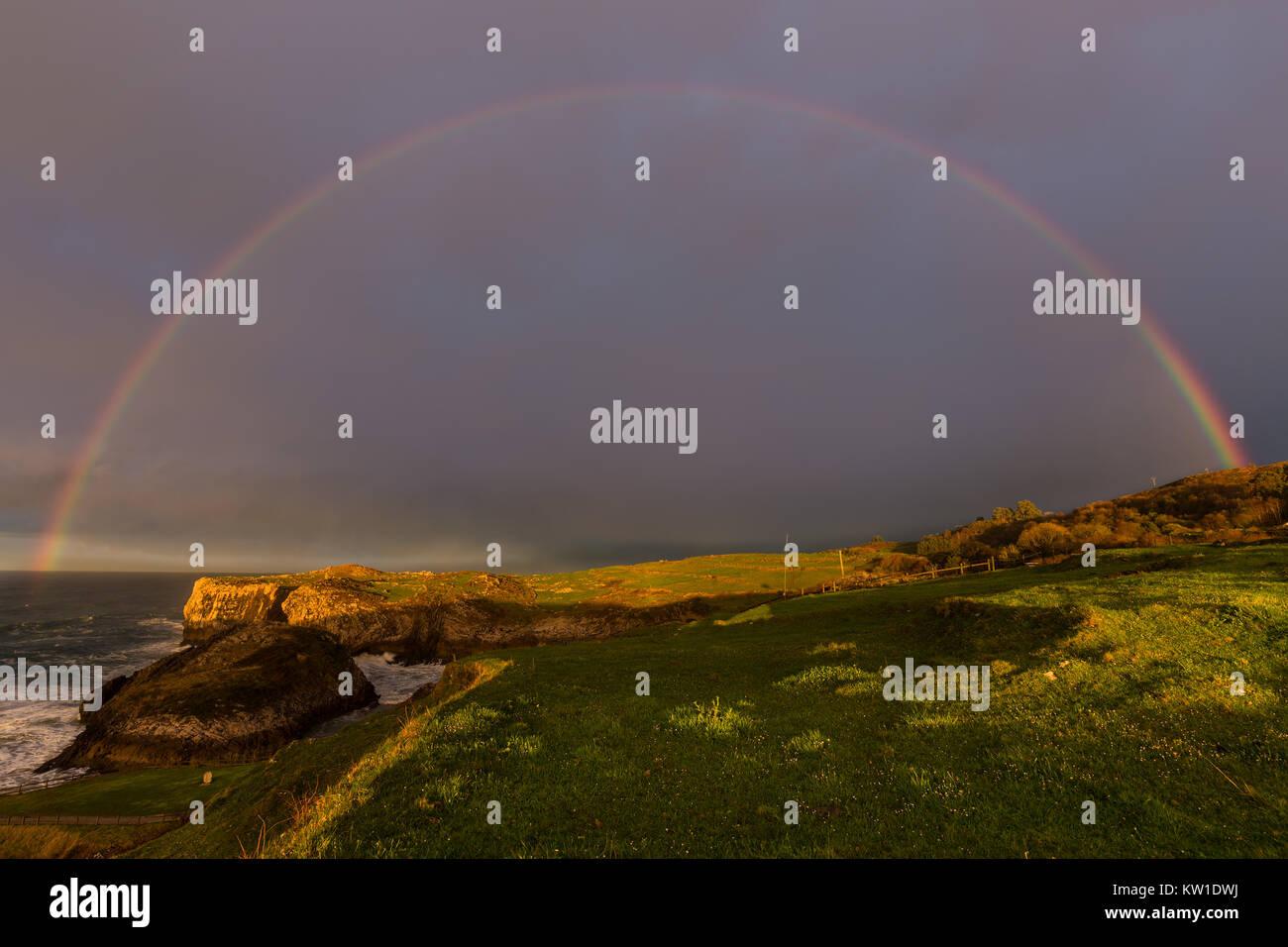 Rainbow over the Asturian coast, near Cue. Spain. - Stock Image