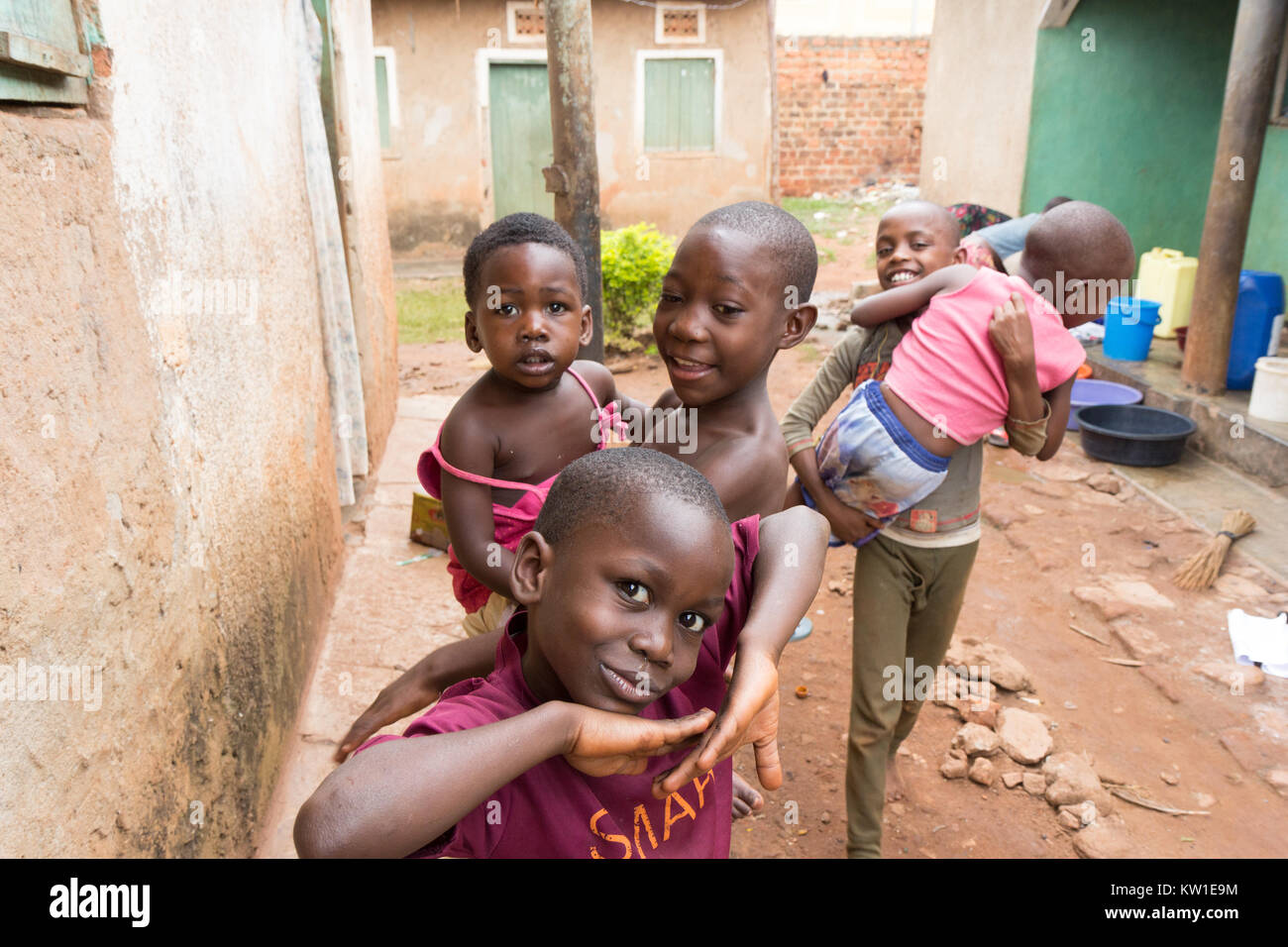 Lugazi, Uganda. June 09 2017. Young African boys holding their siblings in their arms. Girls in the background are - Stock Image