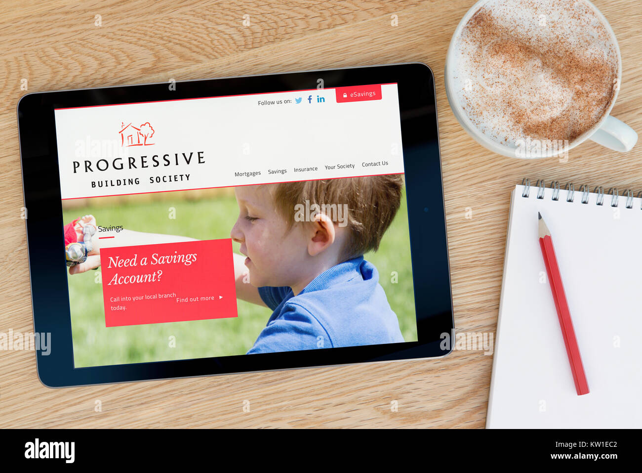 The Progressive Building Society website on an iPad tablet device, resting on a wooden table beside a notepad, pencil - Stock Image