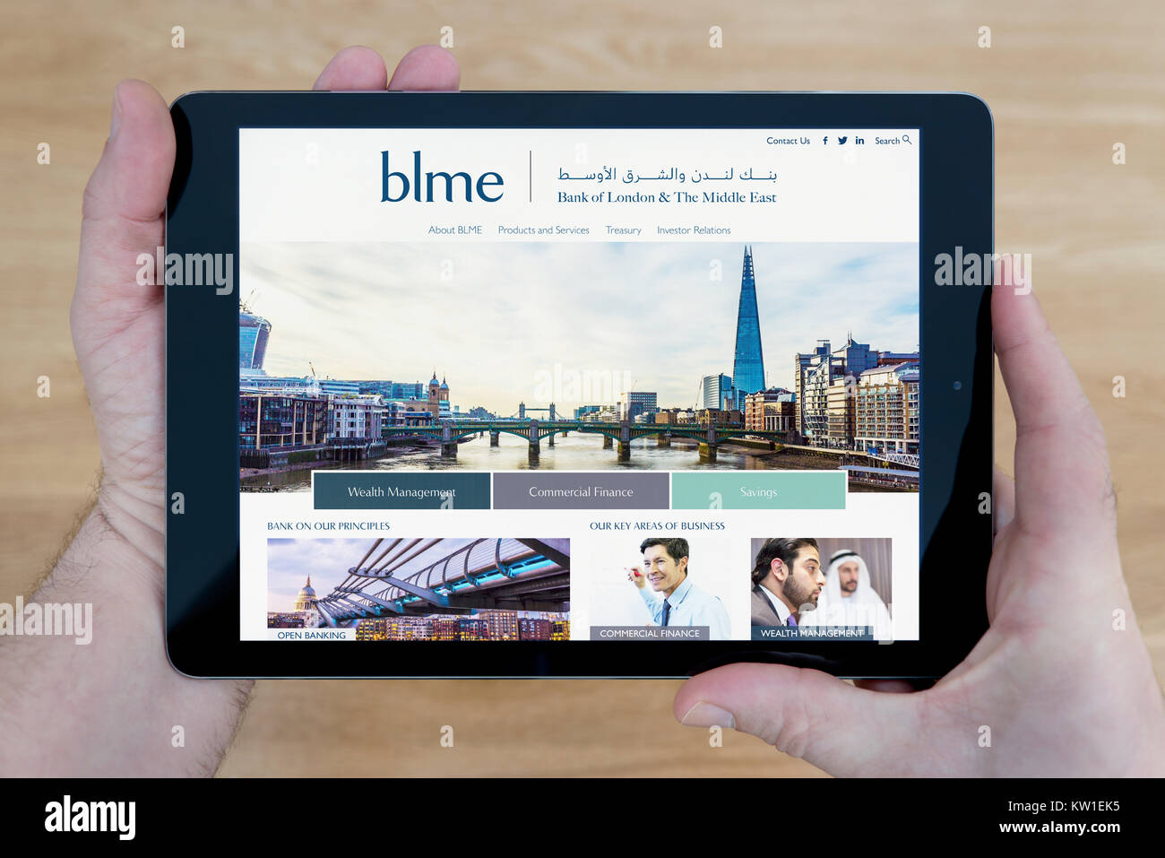A man looks at the Bank of London and the Middle East (BLME) website on his iPad tablet device, on a wooden table - Stock Image