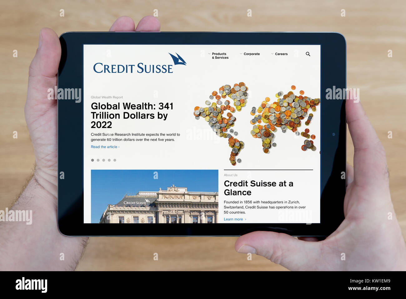 A man looks at the Credit Suisse Bank website on his iPad tablet device, shot against a wooden table top background - Stock Image