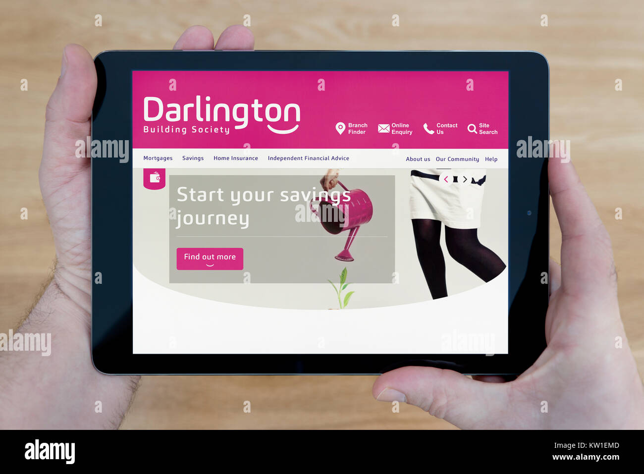A man looks at the Darlington Building Society website on his iPad tablet device, shot against a wooden table top - Stock Image