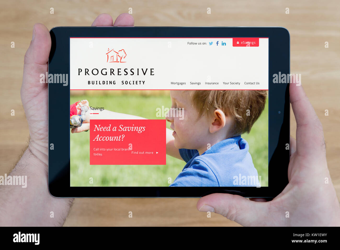 A man looks at the Progressive Building Society website on his iPad tablet device, shot against a wooden table top - Stock Image