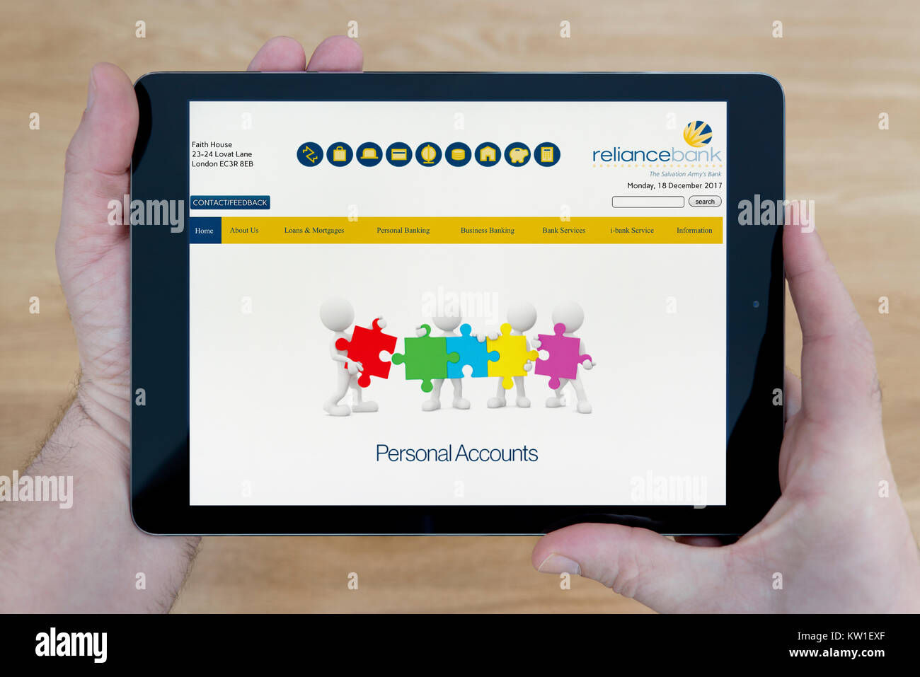 A man looks at the Reliance Bank website on his iPad tablet device, shot against a wooden table top background (Editorial - Stock Image