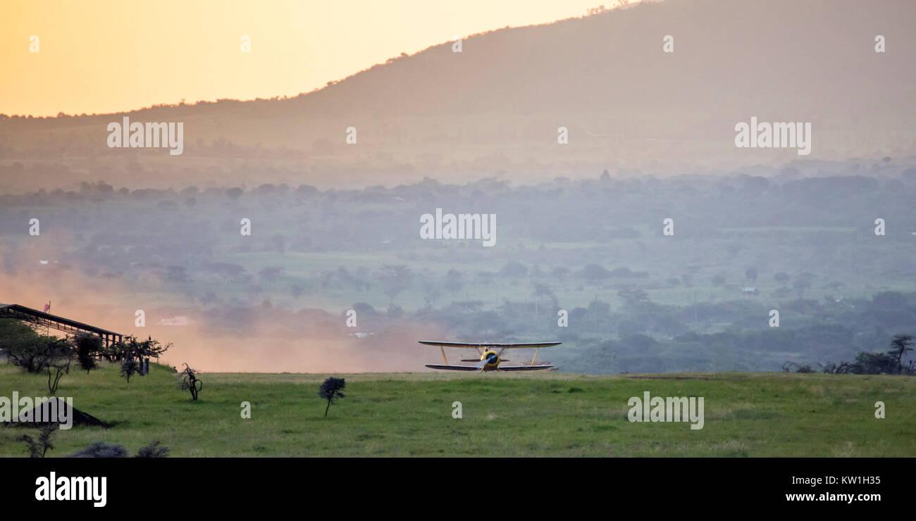 A 1930's Waco biplane flying at dawn over Lewa Wilderness, Lewa Conservancy, Kenya, Africa - Stock Image