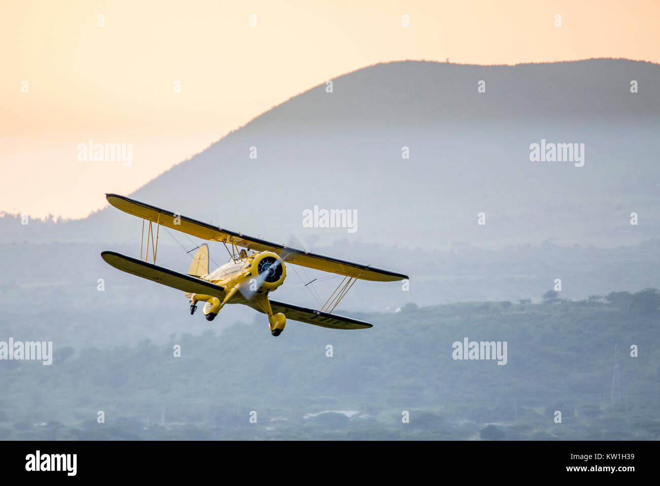 A 1930's Waco biplane flying at dawn over Laikipia, low and towards camera, Lewa Wilderness, Lewa Conservancy, - Stock Image