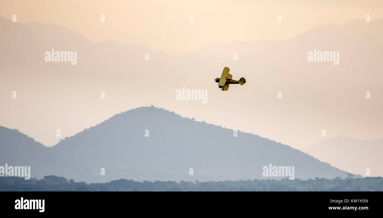 A 1930's Waco biplane flying at dawn over Laikipia, distant view in warm haze, Lewa Wilderness,Lewa Conservancy, - Stock Image