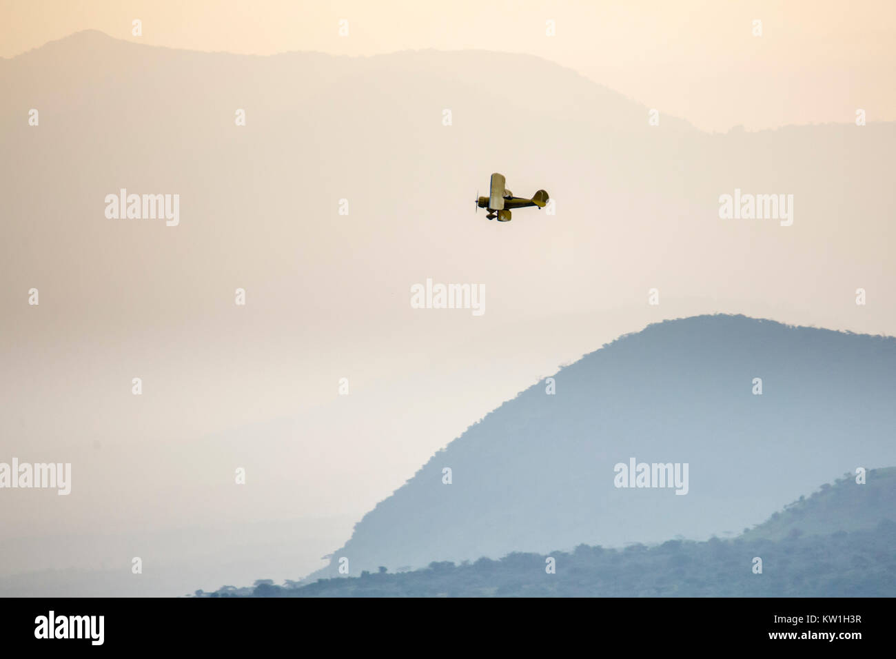 A 1930's Waco biplane flying at dawn over Laikipia, distant view in warm and cool haze, Lewa Wilderness, Lewa - Stock Image