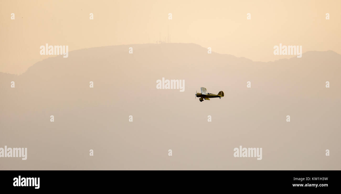 A 1930's Waco biplane flying at dawn over Laikipia, distant view in warm haze,Lewa Wilderness,Lewa Conservancy, - Stock Image
