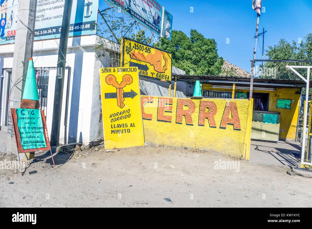 multiple bright vividly colored attention getting sign signs inform passing motorists drivers to small Mexican locksmith - Stock Image