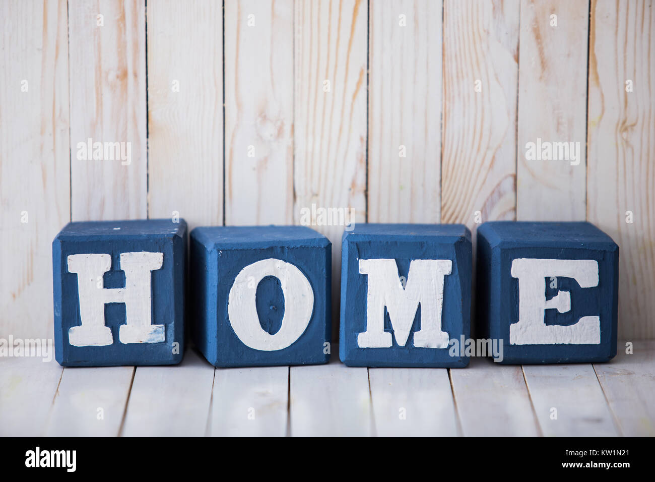 HOME sign made of wooden blocks on wooden background - Stock Image