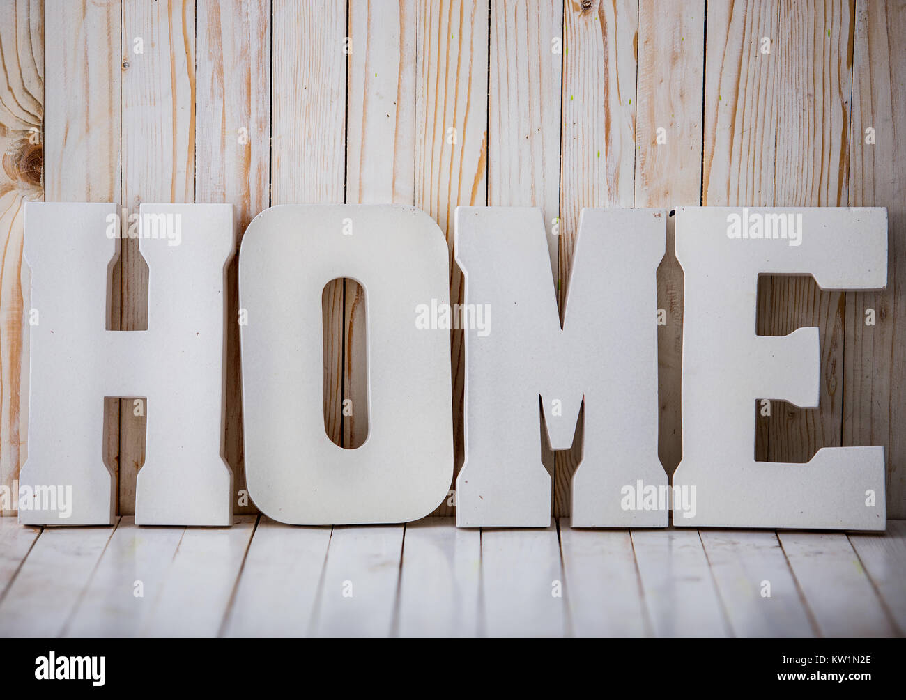 White HOME sign on wooden background - Stock Image