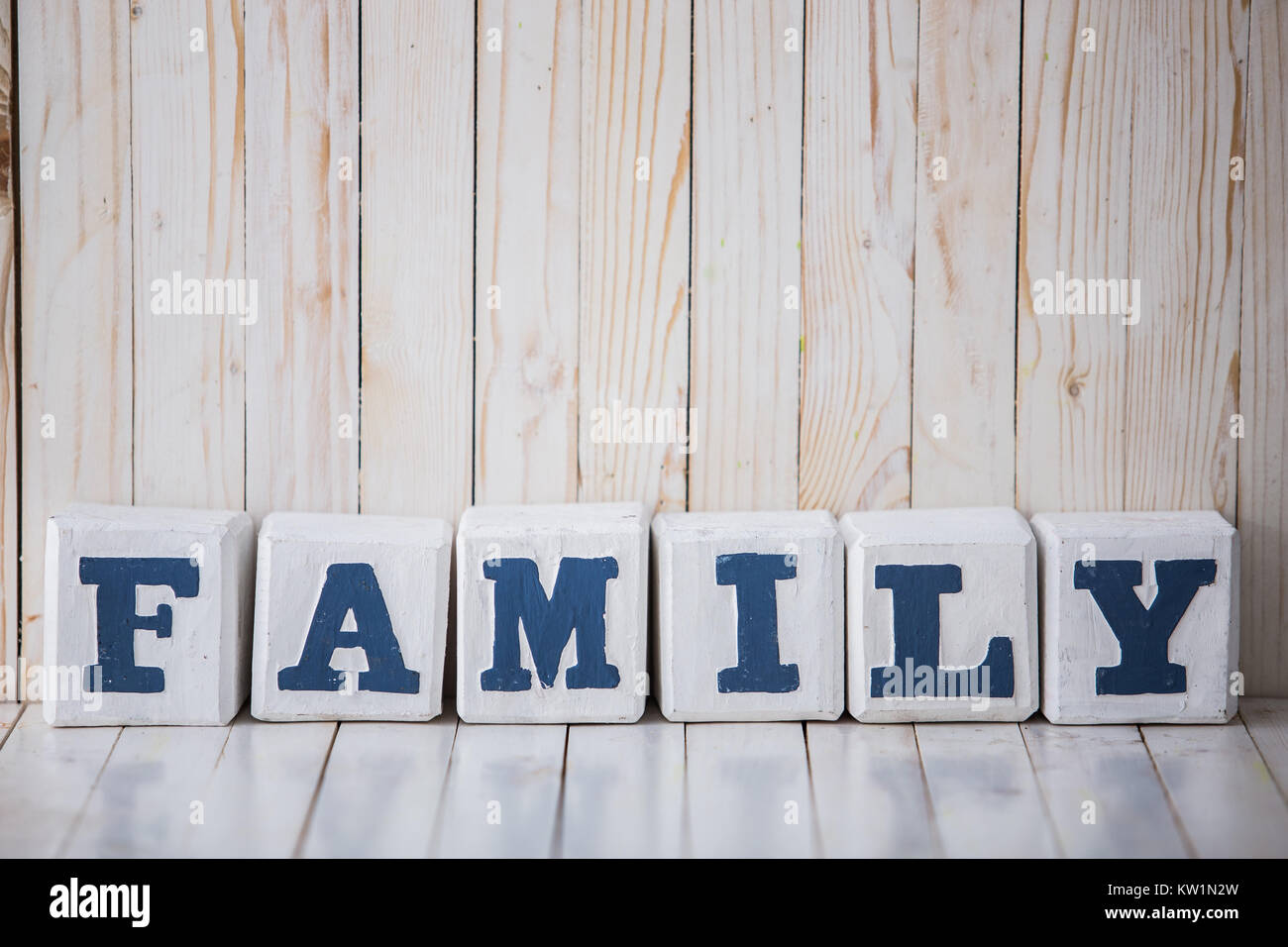 FAMILY sign made of wooden blocks on wooden background - Stock Image