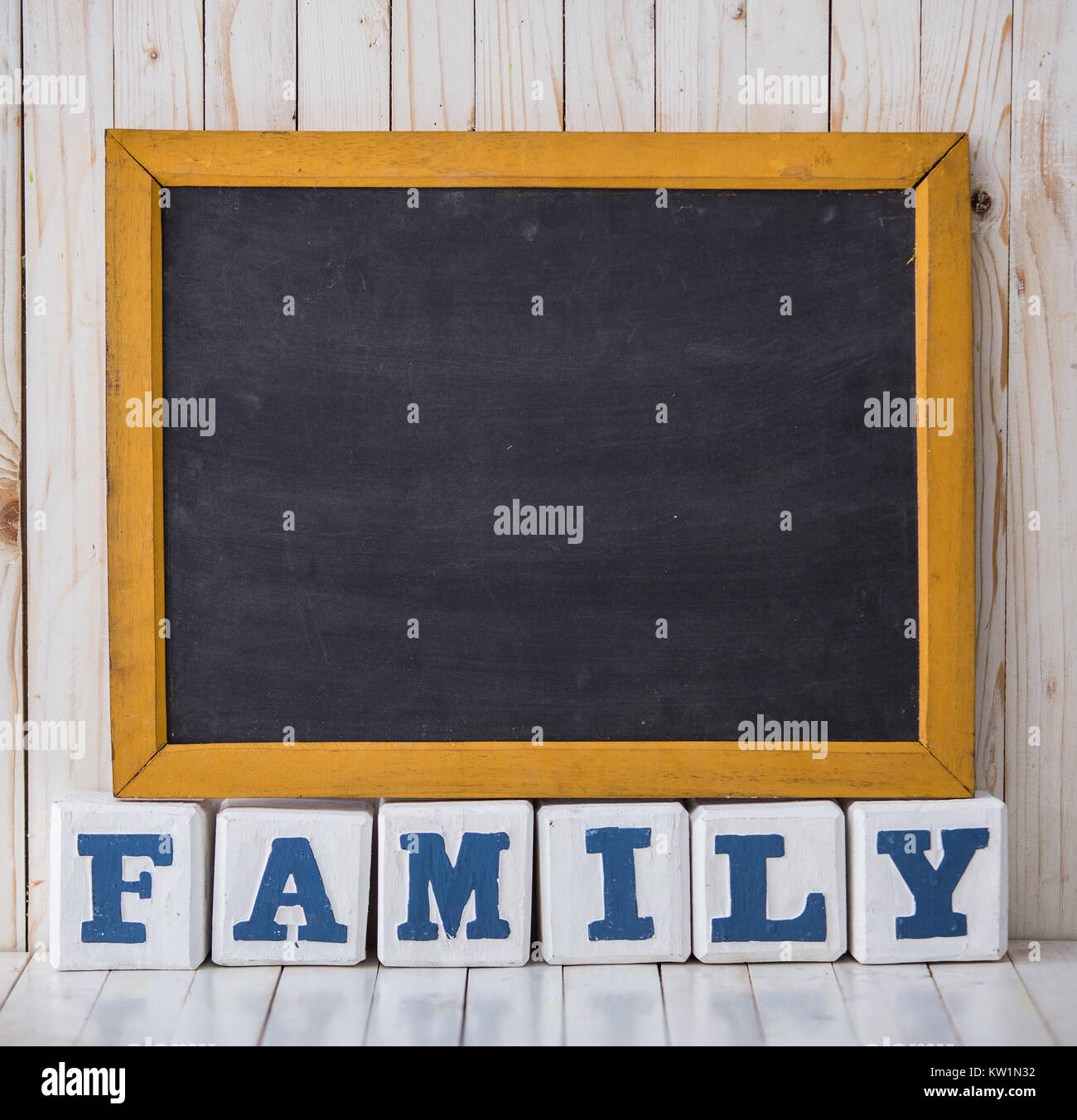 Chalkboard and FAMILY sign made of wooden blocks on wooden backg - Stock Image