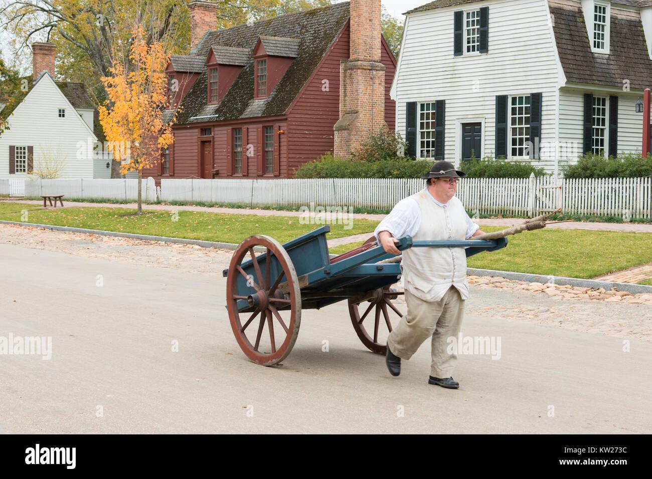 Costumed interpreter pulling handcart on Duke of Gloucester Street. - Stock Image